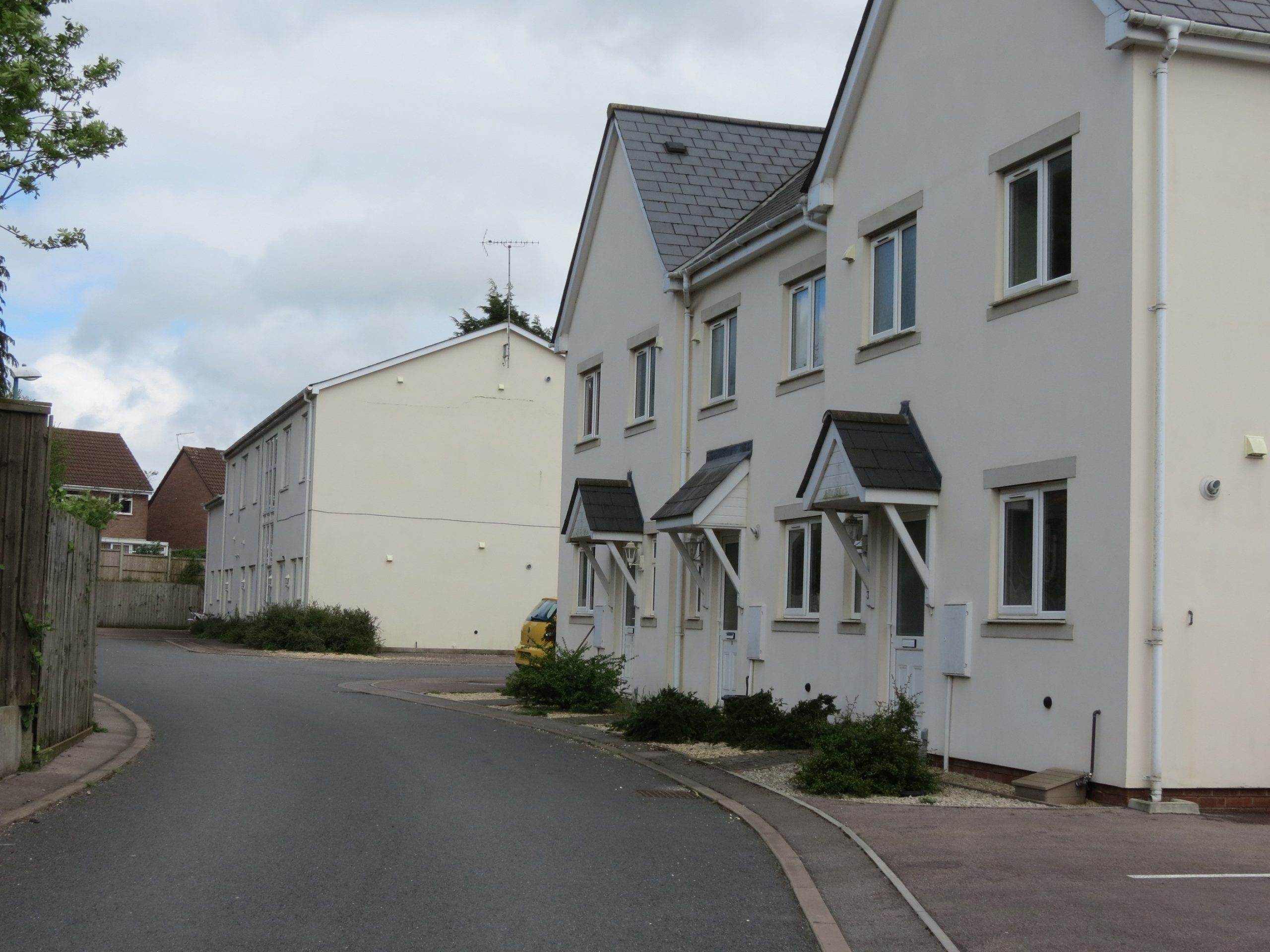 Newly built white houses facing an empty road at The Old Bakery, Bream, Gloucestershire at